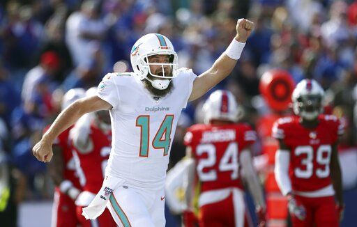 Miami Dolphins quarterback Ryan Fitzpatrick celebrates his touchdown pass to DeVante Parker in the first half of an NFL football game against the Buffalo Bills, Sunday, Oct. 20, 2019, in Orchard Park, N.Y.