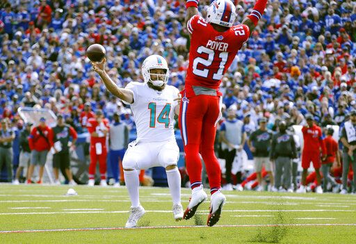 Miami Dolphins quarterback Ryan Fitzpatrick, left, passes under pressure from Buffalo Bills safety Jordan Poyer in the first half of an NFL football game, Sunday, Oct. 20, 2019, in Orchard Park, N.Y.