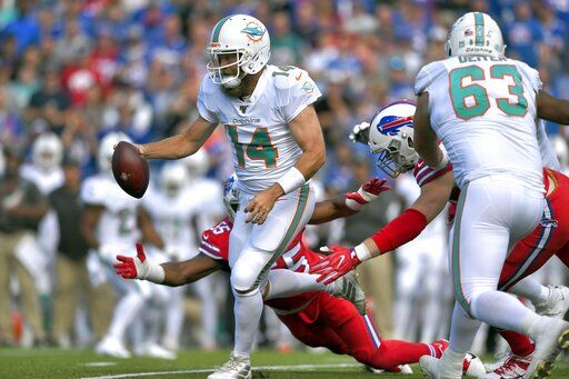 Miami Dolphins quarterback Ryan Fitzpatrick (14) tries to scramble away from Buffalo Bills defensive end Jerry Hughes (55) in the first half of an NFL football game, Sunday, Oct. 20, 2019, in Orchard Park, N.Y.