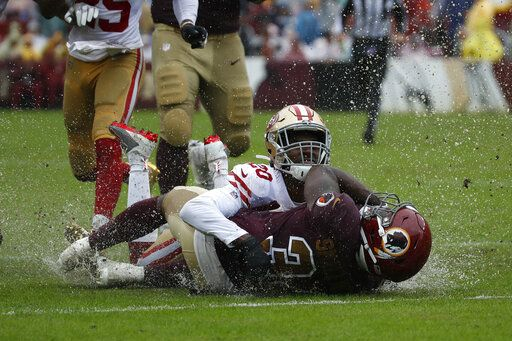 Rain water splashes as San Francisco 49ers cornerback Jimmie Ward (20) tackles Washington Redskins running back Wendell Smallwood in the first half of an NFL football game, Sunday, Oct. 20, 2019, in Landover, Md.