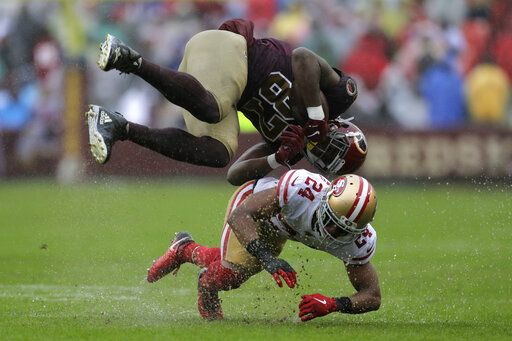 Washington Redskins tight end Jeremy Sprinkle, top, flips over San Francisco 49ers defensive back K'Waun Williams as he rushes the ball in the second half of an NFL football game, Sunday, Oct. 20, 2019, in Landover, Md.
