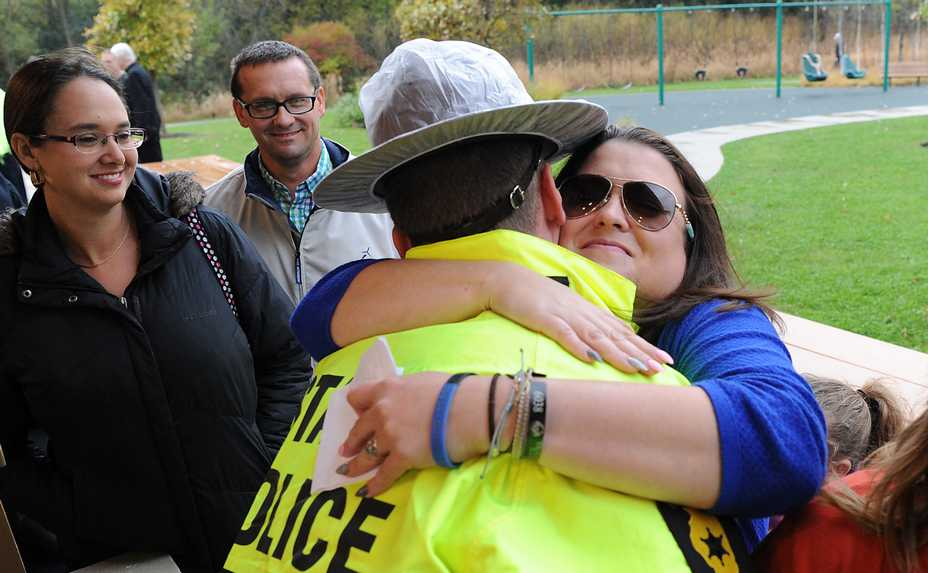 Illinois State Trooper Thomas Brengel hugs Stacy Ellis before the start of a ceremony dedicating a half-mile section of Interstate 94 in Green Oaks in memory of her husband, Illinois State Trooper Gerald W. Ellis of Antioch.