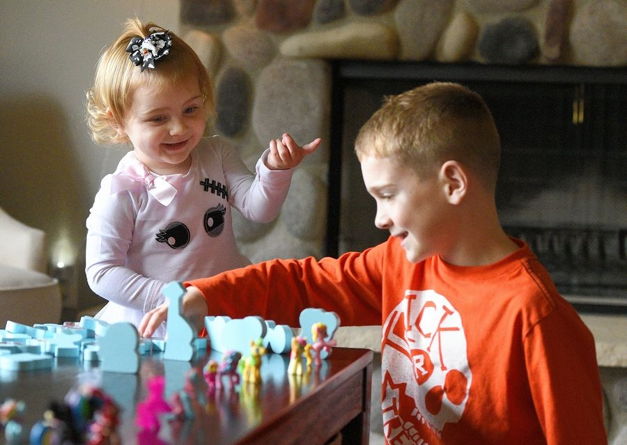 Everly Backe, 2, of Crystal Lake plays with her brother Jack, 7, at their home Thursday. Born with a congenital heart defect, Everly has been in and out of the hospital since she was born, and her family continues to receive support from the Ronald McDonald House Charities. Jack is collecting pop tabs to raise money for the charity.