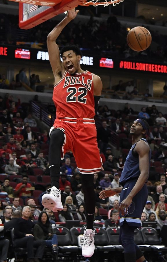 Chicago Bulls forward Otto Porter Jr. (22) reacts after dunking the ball as Memphis Grizzlies forward Justin Holiday (7) stands nearby during the second half of an NBA basketball game, Wednesday, Feb. 13, 2019, in Chicago.