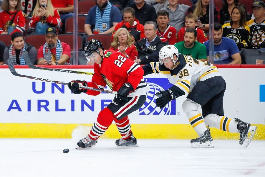 Chicago Blackhawks center Ryan Carpenter, left, keeps the puck away from Boston Bruins center Ryan Fitzgerald, right, during the first period of a preseason NHL hockey game Saturday, Sept. 21, 2019, in Chicago.