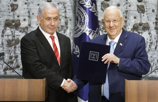 FILE - In this  Sept. 25, 2109 file photo, Israeli President Reuven Rivlin, right, shakes hands with Israeli Prime Minister Benjamin Netanyahu in Jerusalem. Rivlin said Monday, Oct. 21, 2019, that Prime Minister Benjamin Netanyahu has ended his quest to form a new coalition government -- a step that pushes the country into new political uncertainty. Netanyahu fell short of securing a 61-seat parliamentary majority in last month's national election.