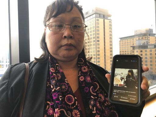 Rena Sapp, outside a courtroom Monday, Oct. 21, 2019, in Anchorage, Alaska, shows a photo of her sister, Veronica Abouchuk, taken during a day out shopping in 2013. Sapp attended the arraignment of Brian Steven Smith, who is accused of killing Abouchuk.