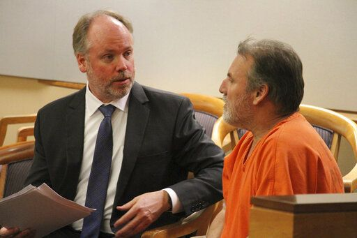 Public defender Dan Lowery, left, talks to his client, Brian Steven Smith, in a courtroom in Anchorage, Alaska, Monday, Oct. 21, 2019. Smith entered an innocent plea Monday in an Anchorage courtroom. He earlier pleaded not guilty in the death of 30-year-old Kathleen Henry, a homeless Alaska Native woman. During his interrogation, police say he confessed to killing another Alaska Native woman. Police won't say if there may be other victims.
