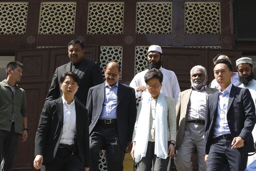 Hong Kong Chief Executive Carrie Lam, center, leaves a mosque in Hong Kong, Monday, Oct. 21, 2019. Lam and other officials apologized to leaders of the Kowloon Mosque after riot police sprayed the building's gate and some people nearby with a blue-dyed liquid from a water cannon as they tried to contain pro-democracy demonstrations Sunday.