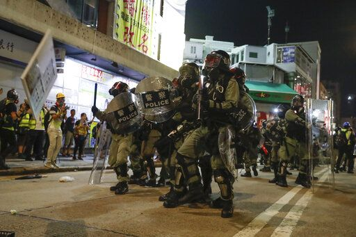 Riot police clash with protesters on the street of Yuen Long, Hong Kong, Monday, Oct. 21, 2019. A evening sit-in at a suburban train station on the three-month anniversary of a violent attack there on protesters by men with suspected organized crime ties.
