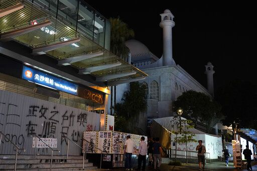 People walk past a mosque next to a subway station at a main road in Hong Kong Sunday, Oct. 20, 2019, Hong Kong. A water cannon truck and armored car led a column of dozens of police vans up and down Nathan Road, a major artery lined with shops, to spray a stinging blue-dyed liquid as police moved to clear the road of protesters and barricades.