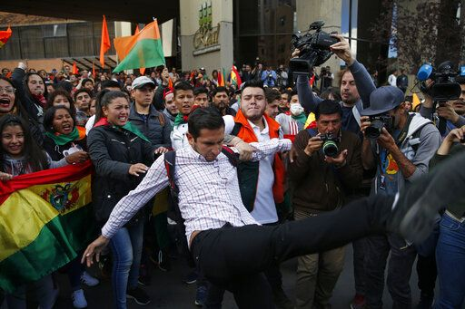 Supporters of opposition presidential candidate Carlos Mesa, a former president, hold back a fellow supporter trying to kick supporters of Bolivian President Evo Morales, who is running for a fourth term, as rival groups gather outside the Supreme Electoral Court where election ballots are being counted in La Paz, Bolivia, Monday, Oct. 21, 2019. A sudden halt in release of presidential election returns led to confusion and protests in Bolivia on Monday as opponents suggested officials were trying to help Morales avoid a risky runoff.