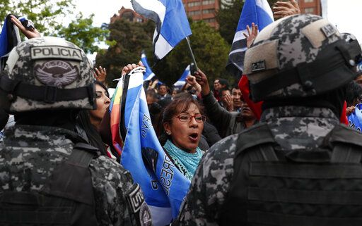 Police stand guard as supporters of Bolivian President Evo Morales, who is running for a fourth term, rally outside the Supreme Electoral Court where election ballots are being counted in La Paz, Bolivia, Monday, Oct. 21, 2019. A sudden halt in release of presidential election returns led to confusion and protests in Bolivia on Monday as opponents suggested officials were trying to help Morales avoid a risky runoff.
