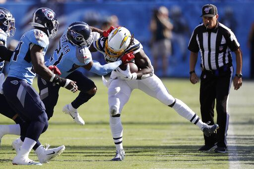 Los Angeles Chargers running back Melvin Gordon, center, is pushed out of bounds by Tennessee Titans cornerback Malcolm Butler (21) in the first half of an NFL football game Sunday, Oct. 20, 2019, in Nashville, Tenn.