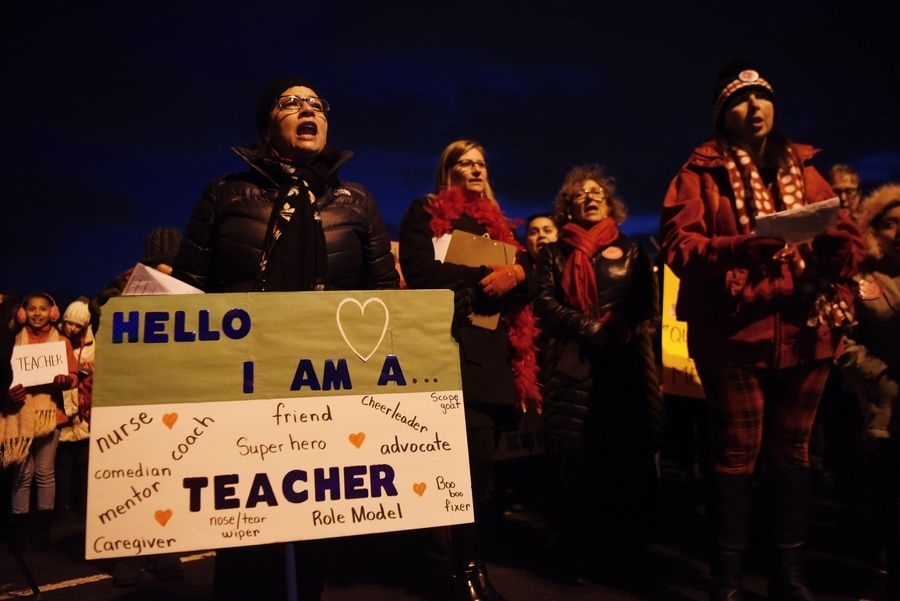 Fullerton Elementary School dual-language kindergarten teacher Luz Chavez, left, chants slogans with fellow teachers in Addison Elementary District 4 as they rally Tuesday in the parking lot of Venuti's Italian Restaurant. Teachers could go on strike as early as Thursday.