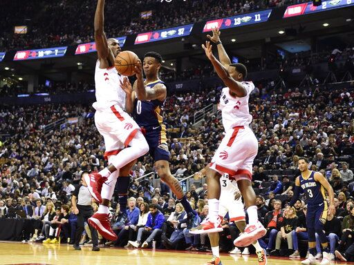 New Orleans Pelicans guard Nickeil Alexander-Walker (0) throws a pass past Toronto Raptors forward Serge Ibaka, left, during the second half of an NBA basketball game Tuesday, Oct. 22, 2019, in Toronto. (Frank Gunn/The Canadian Press via AP)