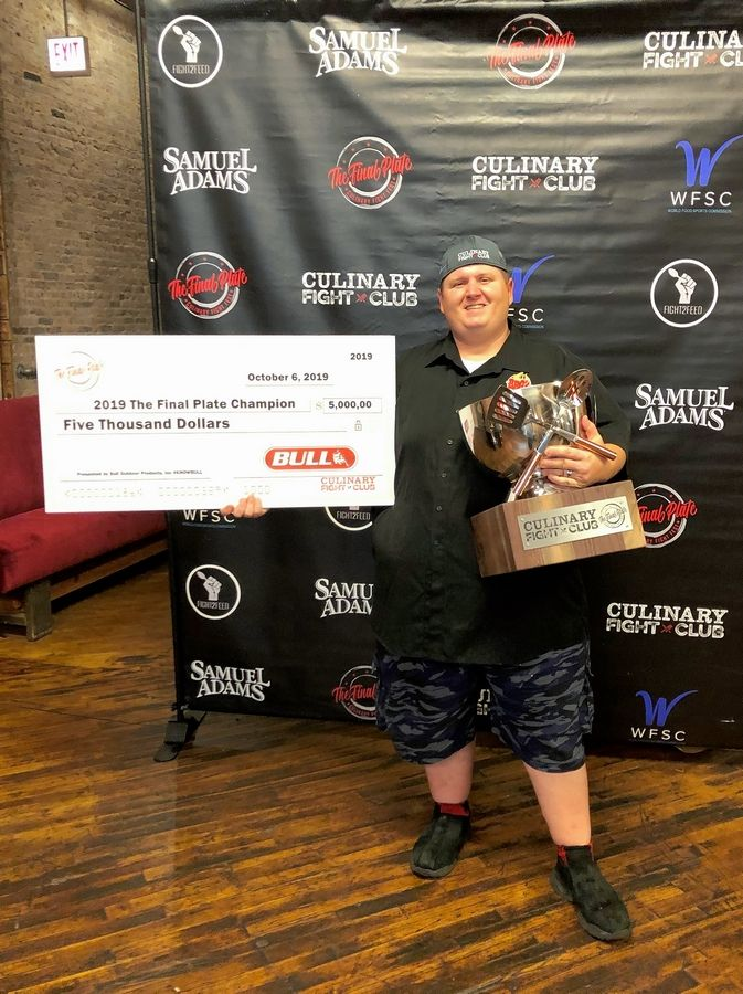 "Chef Kris Schoenberger, owner of BBQ'd Productions in Lake Zurich and Third Lake, shows off his trophy and prize after winning the ""Final Plate"" competition at Culinary Fight Fest at Lacuna Lofts in Chicago earlier this month."