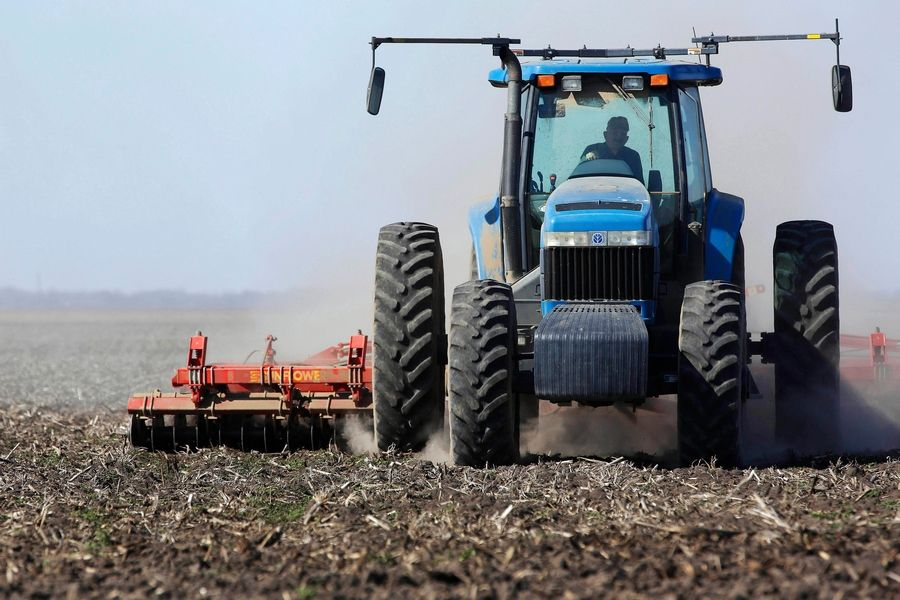 An Illinois corn and soybean farmer cultivates his field in preparation for planting. Wet weather brought late planting and lower yields.