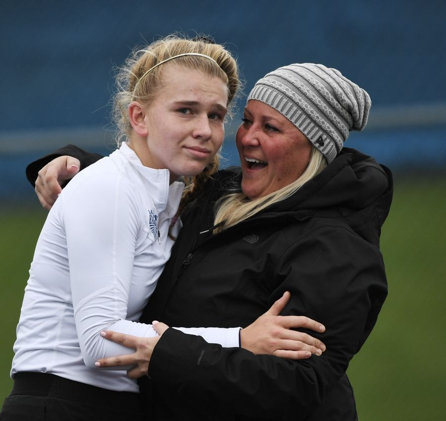 Lakes' Megan Heuser gets a hug from assistant coach Cathryn Ingram after winning the girls state tennis Class 1A championship at Buffalo Grove High School Saturday.