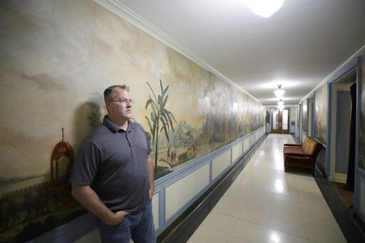 In this Aug. 26, 2019, photo Jim Chumbley stands in front of the recently restored mural in the main floor for of the Decatur Masonic Temple in Decatur, Ill. (Jeff Smudde/Herald & Review via AP)