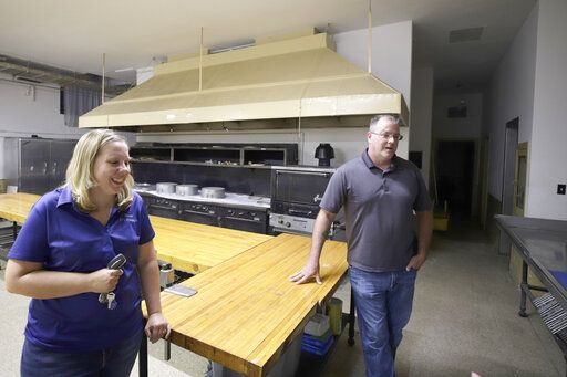 In this Aug. 26, 2019, photo Mindy Oakley, left, and Jim Chumbley, right, stand in the kitchen of the Decatur Masonic temple in Decatur, Ill. (Jeff Smudde/Herald & Review via AP)