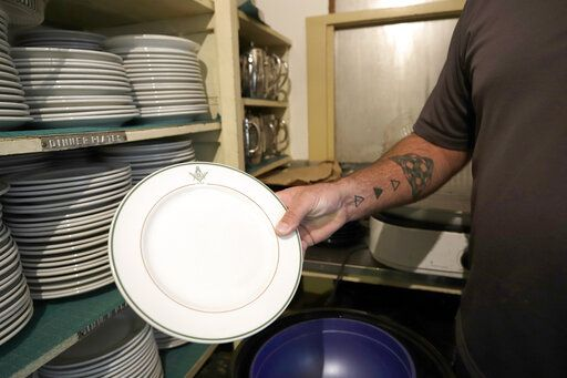 In this Aug. 26, 2019, photo Jim Chumbley shows one of the plates in the dish room of the Decatur Masonic Temple in Decatur, Ill. (Jeff Smudde/Herald & Review via AP)