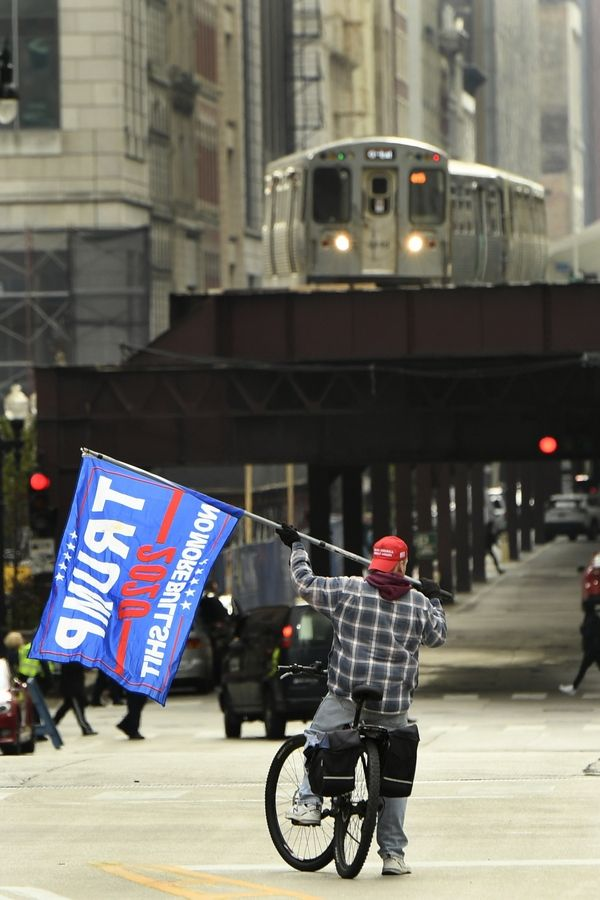 Trump supporter Joe Loris of Berwyn flies a Trump flag while riding his bike near protesters gathered across the Chicago River from the Trump International Hotel and Tower in Chicago while President Trump attends a fundraiser there Monday.