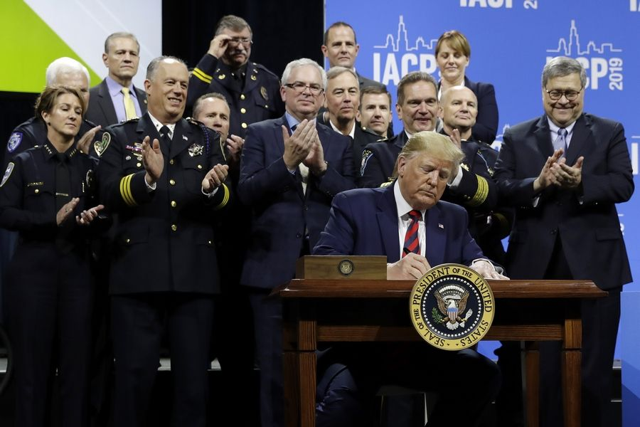 President Donald Trump signs an executive order during a speech to the International Association of Chiefs of Police Monday at McCormick Place in Chicago. Buffalo Grove Police Chief Steven R. Casstevens, who will become IACP president on Tuesday, is front row, second from left. U.S. Attorney General William Barr is at far right.