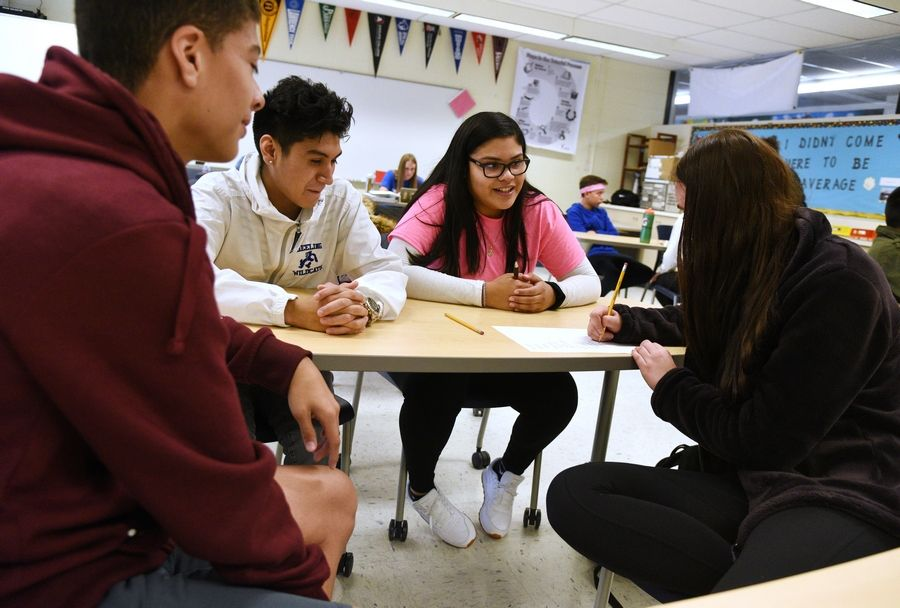 Wheeling High School juniors, from left, Brian Aguirre-Lorenzo, Alex Ramos Perez, Maria Escanuela and Liza Tkachuk work on a list of ways people communicate during a technology exercise in their Advancement Via Individual Placement, or AVID, program class. It's among the costlier programs at the school.