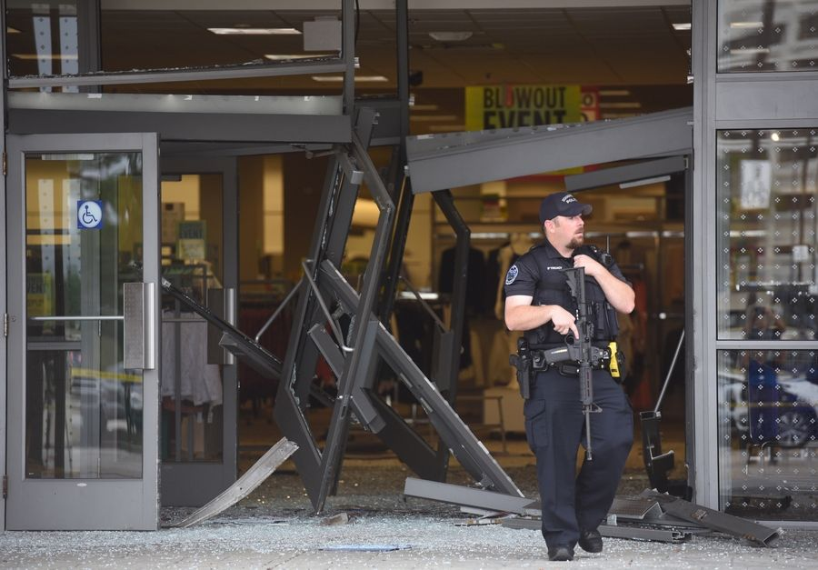 A Schaumburg police officer stands guard where a man drove an SUV through a Sears entrance and into Woodfield Mall on Sept. 20.