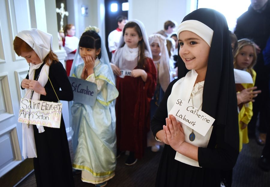 Katelyn Beckmann, right, portrays St. Catherine Laboure and Avery Delany, far left, is dressed as St. Elizabeth Ann Seton as first-graders await the processional of the All Saints Day Mass at St. James Catholic Church in Arlington Heights Friday.