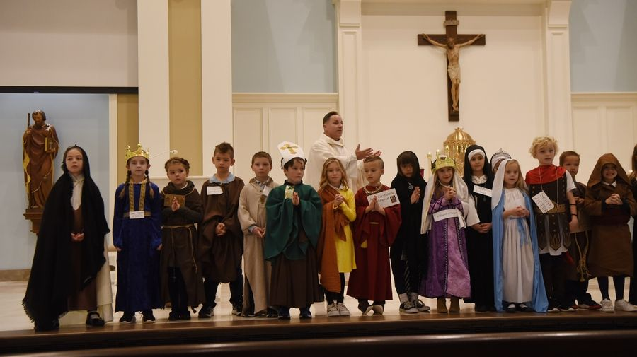 First-graders dressed as saints line up in front of the altar as the Rev. Matt Foley gives the homily Friday during the All Saints Day Mass at St. James Catholic Church in Arlington Heights.