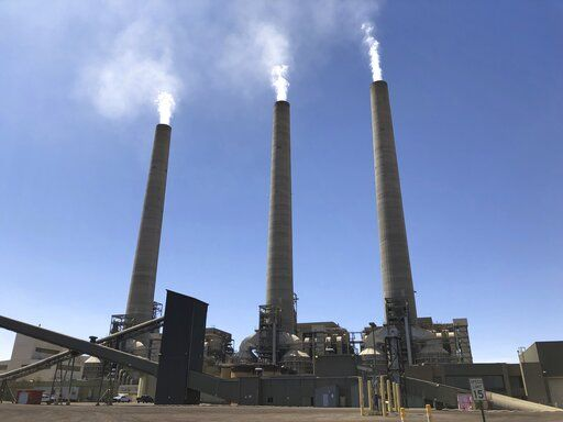 This Aug. 20, 2019, image shows a trio of concrete stacks at the Navajo Generating Station near Page, Ariz. The power plant will close before the year ends, upending the lives of hundreds of mostly Native American workers who mined coal, loaded it and played a part in producing electricity that powered the American Southwest.