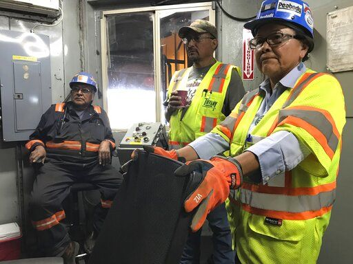 This Aug. 20, 2019, image shows employees with Peabody Energy and the Navajo Generating Station talking about the pending closure of the mine and power plant during a tour of a coal silo near Kayenta, Ariz. The Navajo Generating Station near Page, Arizona, will close before the year ends and other coal-fired plants in the region are on track to shut down or reduce their output in the next few years.