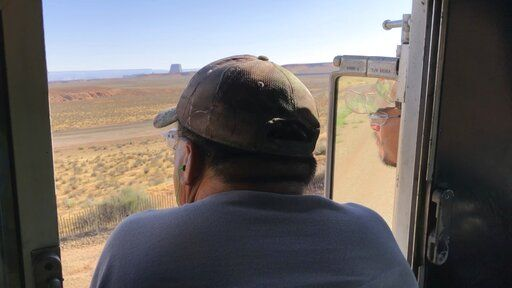 In this Aug. 20, 2019, image, train operator Ron Little is reflected in the rear view mirror as he leans out the window to get a better look at the mile-long coal train as it leaves the Navajo Generating Station near Page, Ariz. The power plant will close before the year ends, upending the lives of hundreds of mostly Native American workers who mined coal, loaded it and played a part in producing electricity that powered the American Southwest.