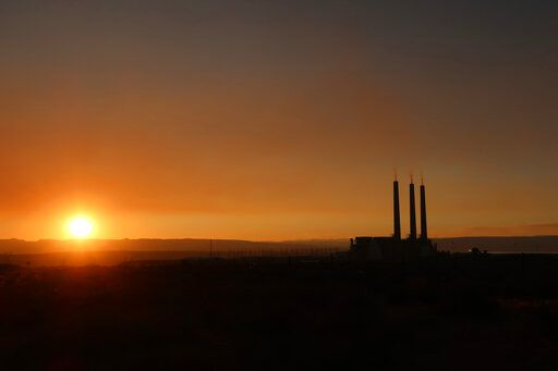 This Aug. 19, 2019, image shows the sun setting behind the coal-fired Navajo Generating Station near Page, Ariz. The power plant will close before the year ends, upending the lives of hundreds of mostly Native American workers who mined coal, loaded it and played a part in producing electricity that powered the American Southwest.