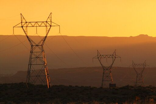 This Aug. 20, 2019, image shows transmission lines leading from the Navajo Generating Station near Page, Ariz. The power plant will close before the year ends. Other coal-fired plants in the region and in the U.S. are on track to shut down or reduce output as utilities turn to natural gas and renewable energy.
