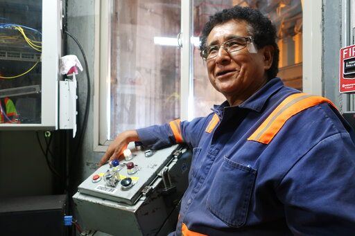 In this Aug. 20, 2019, image, Peabody Energy silo operator Gerald Clitso talks with coworkers after loading coal into a train bound for the Navajo Generating Station near Page, Ariz. The power plant will close before the year ends, upending the lives of hundreds of mostly Native American workers who mined coal, loaded it and played a part in producing electricity that powered the American Southwest.