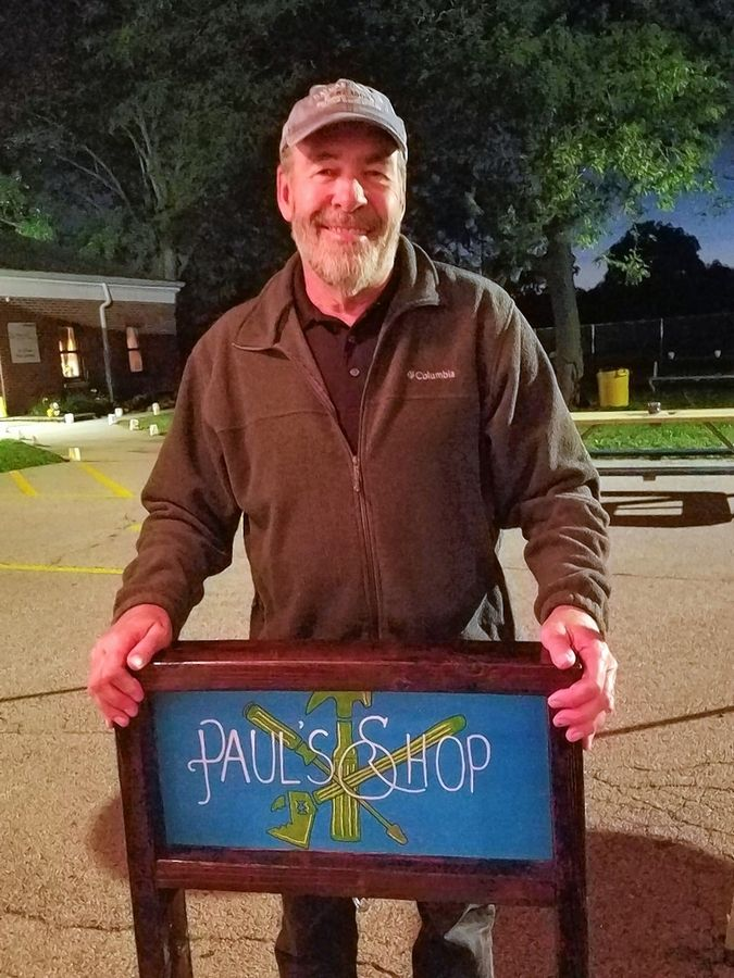 Paul Bartholomae holds the sign handcrafted and presented to him by his Jen School building-trade students. The faculty and students wanted to show Bartholomae how much they appreciate him.