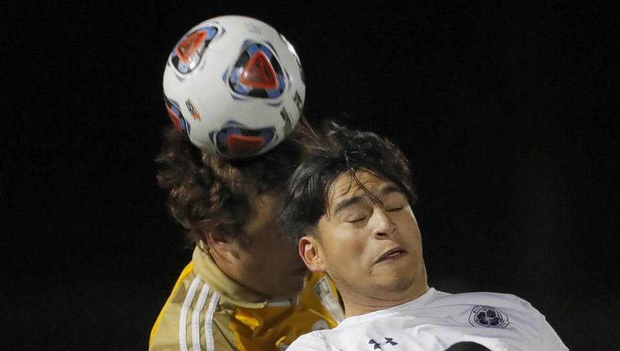 West Chicago's Jessie Hernandez heads the ball in front of Jacobs' Sam Colucci during supersectional boys soccer action at Charlie O. Feutz Field on the campus of Conant High School in Hoffman Estates Tuesday night.