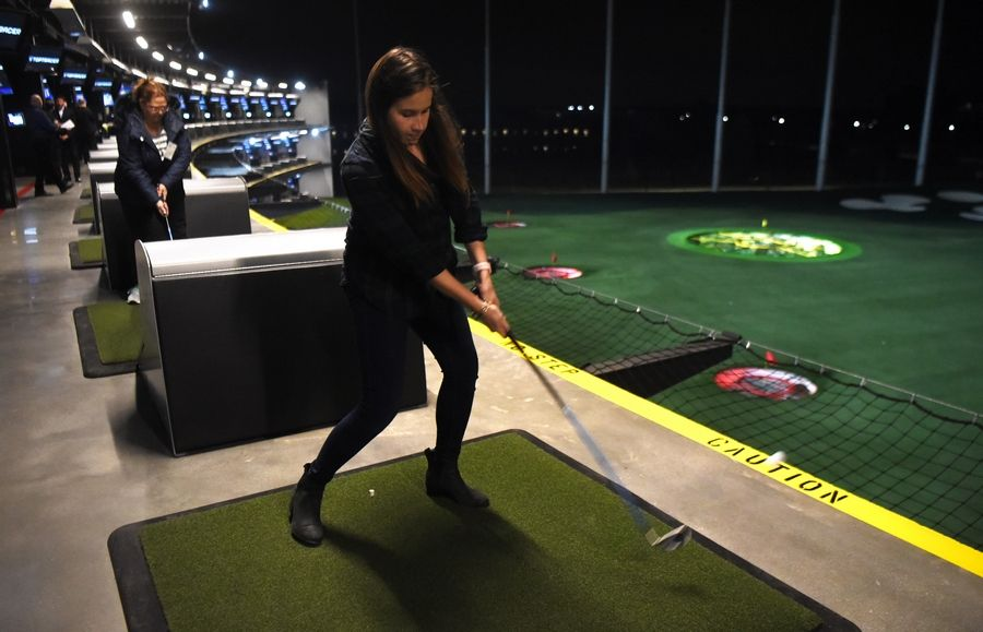 Niki Sabatino of Naperville hits a ball from the third level during a preview event Wednesday for the new Topgolf facility in Schaumburg.