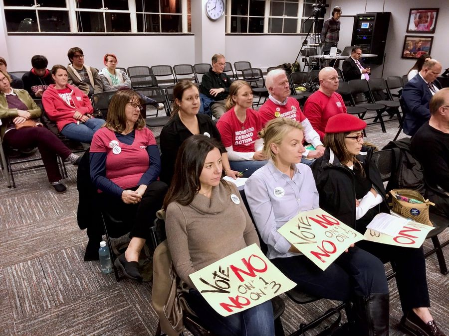 Moms Demand Action for Gun Sense In America members urged the District 220 board on Tuesday night to discourage the idea that local districts should be able to decide whether to permit armed staff members.