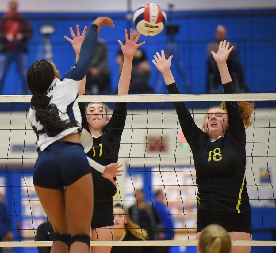 Fremd's Rian Baker and Allie Belmonte try to block a shot by Glenbrook South's Kendall Smith in the girls volleyball sectional final match in Park Ridge Wednesday.
