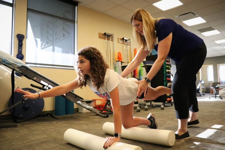 Emma Dixon is guided by physical therapist Kim Lueken, PT, DPT, OCS, through a series of hip exercises at Northwestern Medicine Rehabilitation Services Glen EllynCourtesy of Kim Waterman