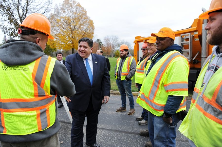 Gov. J.B. Pritzker meets with road construction workers Wednesday during a visit to Lombard.