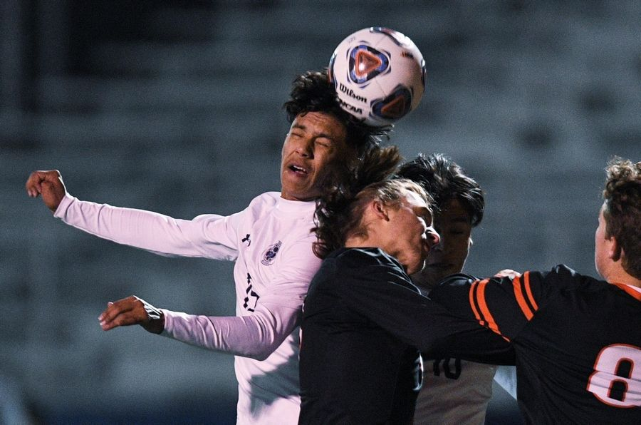 West Chicago's Alejandro Cadena and Jessie Hernandez collide with Edwardsville's Abraham Valle as they go for a header in the Class 3A boys state semifinal game in Hoffman Estates Friday.
