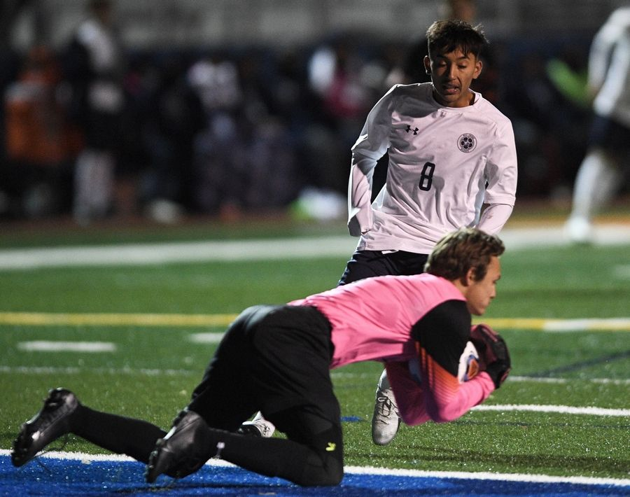 West Chicago's Moises Morfin watches Edwardsville goalkeeper Miguel Johan Sanchez wrap up the ball in the Class 3A boys state semifinal game in Hoffman Estates Friday.