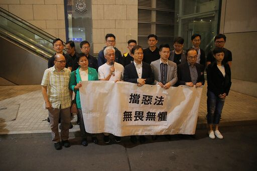 Pro-democracy lawmakers Leung Yiu-chung, third left, Kwok Ka-ki, center, and Gary Fan, third right, protest outside police headquarters against the arrest of their colleagues, holding a banner that reads 'œdefeat the evil law, Fearless'� in Hong Kong, Saturday, Nov. 9, 2019. Three members of the Legislative Council of the Hong Kong Special Administrative Region were arrested for allegedly breaching legislative council regulation earlier this year, Hong Kong police confirmed Saturday. The arrests were made over Friday and Saturday after the police carefully investigated reports of obstruction at a meeting in the Legislative Council Complex on May 11, they told Xinhua.