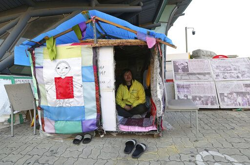 In this April 2, 2019, photo, Choi Seung-woo, a victim of Brothers Home, sits in a tent near the National Assembly in Seoul, South Korea. Choi and a small number of other Brothers Home inmates have been camping out in front of the National Assembly's gate for more than two years calling for lawmakers to pass a bill that would launch a full investigation into past human rights atrocities, including the Brothers Home incident.