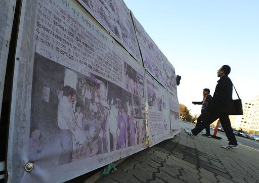In this April 2, 2019, photo,  people walk past a photo of guards unloading children from a truck at the Brothers Home in Busan, as it is displayed in front of National Assembly in Seoul, South Korea. A notorious South Korean facility that kidnapped, abused and enslaved children, adults and the disabled for a generation was also shipping children overseas for adoption, part of a massive profit-seeking enterprise that thrived by exploiting those trapped within its walls, The Associated Press has found.